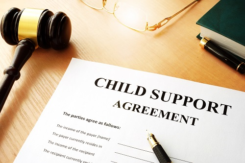 Child support agreement with pens, a gavel, glasses, and a book near by.