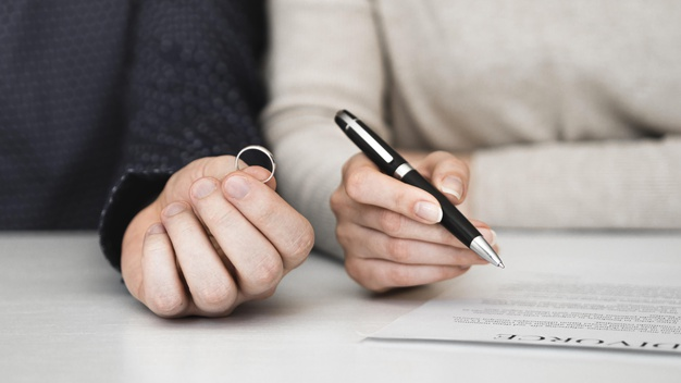 One hand holding a ring, another hand holding a pen poised above a divorce document.