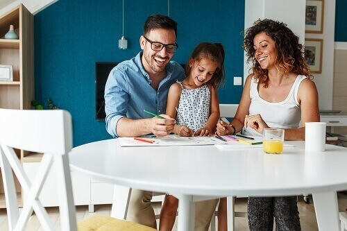 Smiling man, girl and woman sitting around a table coloring.